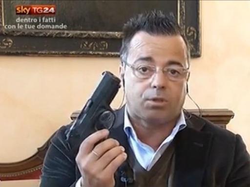 Buonanno con Pistola in Mano durante Intervista